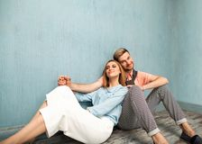 Fashion girl and guy in outlet clothes posing on a blue backgro. Und Stock Images