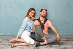 Fashion girl and guy in outlet clothes posing on a blue backgro. Und Royalty Free Stock Image
