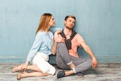 Fashion girl and guy in outlet clothes posing on a blue backgro. Und Royalty Free Stock Photography