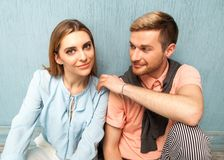 Fashion girl and guy in outlet clothes posing on a blue backgro. Und Royalty Free Stock Images