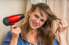Fashion girl with hair dryer dries her hair Royalty Free Stock Photography