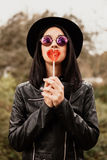 Fashion girl hipster with red lollipop Royalty Free Stock Image
