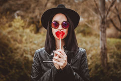 Fashion girl hipster with a red lollipop Stock Photography