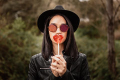 Fashion girl hipster with red lollipop Stock Images