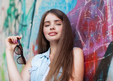 Fashion girl holding glasses. Wall graffiti Royalty Free Stock Images