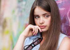 Fashion girl holding glasses. Wall graffiti Stock Photos