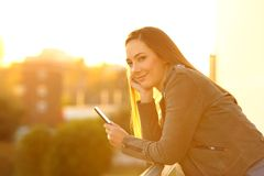 Fashion girl holding a phone looking at camera at sunset stock image