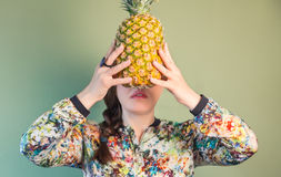 Fashion girl holding pineapple in front of face Stock Photos