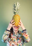 Fashion girl holding pineapple in front of face Royalty Free Stock Photos