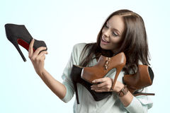 Fashion girl holding shoes assortment Royalty Free Stock Photography