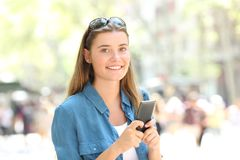 Fashion girl holding smart phone looks at you. Fashion happy girl holding a smart phone looks at you in the street royalty free stock image