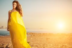 Fashion girl in a long dress against a summer sunset background. royalty free stock images