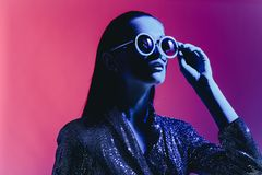 Fashion girl with long hair and round sunglasses in a black shining dress poses in neon light in the studio.  stock image