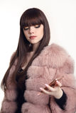 Fashion girl look in pink fur coat holding mobile phone isolated. On white background. Trendy hairstyle. Brown haired Stock Images