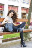 Fashion girl looking message on your smart phone, outdoor. Stock Images