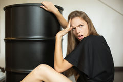 Fashion girl looking omg and sitting next to a black barrel-roll Royalty Free Stock Photography