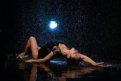 Fashion girl lying in black aqua studio royalty free stock image