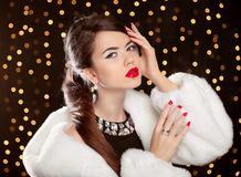 Fashion girl model posing in white fur coat. and luxury jewelry. Royalty Free Stock Photography