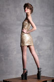 Fashion girl model standing back turned and looking over his shoulder. Royalty Free Stock Images