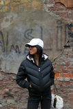 Fashion girl near grungy wall. Young pretty fashion girl standing alone near cracked wall. Wearing snowy white cap Stock Images