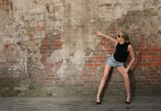 Fashion girl in near the wall. Fashon girl standing near old cracked dirty grunge wall. Please write me where you used this image, model will be glad to know it royalty free stock photos