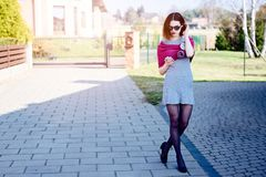 Fashion girl in pink woolen shawl using her smartphone Stock Photos