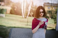 Fashion girl in pink woolen shawl using her smartphone. Fashion girl in pink woolen shawl and grey dress using her smartphone Royalty Free Stock Photography