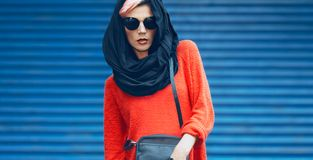 Fashion girl portrait in a stylish black headscarf and sunglasses on a blue background Royalty Free Stock Photo