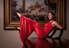 Fashion Girl in Red Dress. Horizontal photo of a fashion girl in a long shiny red dress. She is a brunette, she wears high heels and long gloves, her legs are up Royalty Free Stock Photography