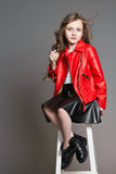 Fashion Girl in a red jacket poses and grimaces and makes a face. Photo Studio on a gray background. Birthday, holiday stock photos