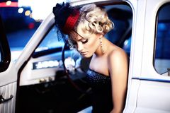 Fashion girl in retro style posing in old car Royalty Free Stock Image