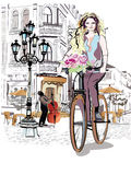 Fashion girl rides a bicycle the streets of the old town. Royalty Free Stock Photos