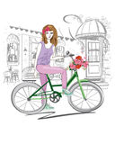 Fashion girl rides a bicycle the streets of the old town. Royalty Free Stock Photography