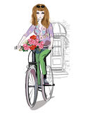 Fashion girl rides a bicycle the streets. Royalty Free Stock Photos