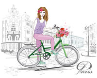 Fashion girl rides a bicycle the streets. Royalty Free Stock Image