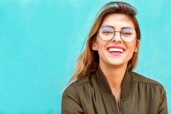 Fashion girl in round glasses stands posing near a turquoise wall. / royalty free stock photos