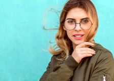Fashion girl in round glasses stands posing near a turquoise wall royalty free stock photography