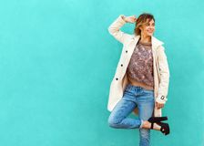 Fashion girl in round glasses stands posing near a turquoise wall.  royalty free stock photography