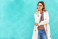 Fashion girl in round glasses stands posing near a turquoise wall royalty free stock photos