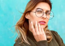 Fashion girl in round glasses stands posing near a turquoise wall stock photography
