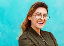 Fashion girl in round glasses stands posing near a turquoise wall stock image