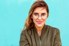 Fashion girl in round glasses stands posing near a turquoise wall.  stock image