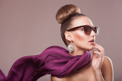 Fashion girl with a scarf. Fashion girl with a purple scarf, wearing sunglasses, updo Royalty Free Stock Photography