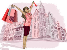 Fashion girl with shopping bags on a city-backgrou Royalty Free Stock Images