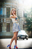 Fashion girl with short skirt , bag and high heels walking on street. Attractive woman with interesting hair walking in the city.Walking fashion model in blue Stock Image