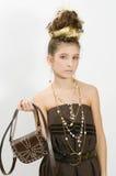 Fashion girl showing jewels and handbag Royalty Free Stock Photos