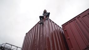 Fashion girl sits on a freight container.  stock video footage