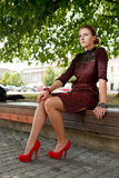 Fashion girl sitting on bench in urban park. Wearing red heels Stock Photo