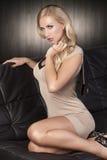 Fashion girl sitting on a black sofa Royalty Free Stock Image