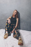 Fashion girl sitting on floor against white wall background. Royalty Free Stock Image